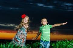 Grupp av lyckliga barn som leker på äng Royaltyfria Bilder