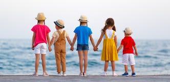 Grupp av lyckliga barn vid havet i sommar royaltyfria bilder