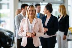 Grupp av lyckliga bilförsäljningskonsulenter som arbetar inom medelvisningslokal arkivbilder