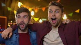 Grupp av lyckliga caucasian vänner som håller ögonen på sportleken i stång som firar seger stock video