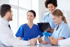 Grupp av lyckliga doktorer som möter på sjukhuskontoret royaltyfria bilder