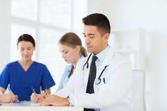 Grupp av lyckliga doktorer som möter på sjukhuskontoret arkivfoton