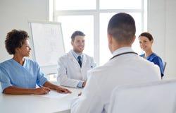 Grupp av lyckliga doktorer som möter på sjukhuskontoret arkivfoto