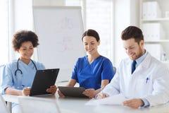 Grupp av lyckliga doktorer som möter på sjukhuskontoret royaltyfri foto