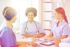 Grupp av lyckliga doktorer som möter på sjukhuskontoret royaltyfria foton