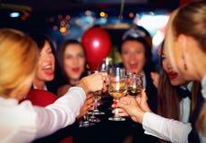 Grupp av lyckliga eleganta kvinnor som klirrar exponeringsglas i limousineet, möhippa Royaltyfria Foton