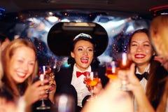 Grupp av lyckliga eleganta kvinnor som klirrar exponeringsglas i limousineet, möhippa Arkivbilder