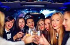 Grupp av lyckliga eleganta kvinnor som klirrar exponeringsglas i limousineet, möhippa Arkivbild