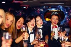Grupp av lyckliga eleganta kvinnor som klirrar exponeringsglas i limousineet, möhippa Royaltyfri Foto