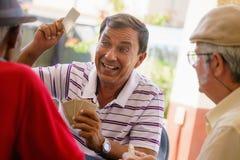 Grupp av lyckliga gamla vänner som spelar kort och att skratta royaltyfria foton