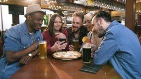 Grupp av lyckliga hipstervänner som tillsammans håller ögonen på videoen, foto på den smarta telefonen i stången, bar lager videofilmer