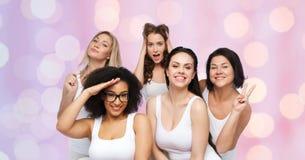 Grupp av lyckliga kvinnor i den vita underkläderna som har gyckel Arkivfoto