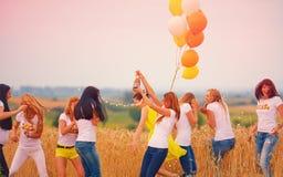 Grupp av lyckliga kvinnor med flaskan av champagne på sommarfält Royaltyfri Foto