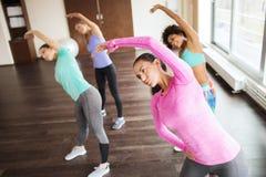 Grupp av lyckliga kvinnor som utarbetar i idrottshall Arkivfoton