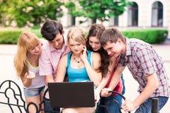 Grupp av lyckliga le tonårs- studenter utanför högskolan Arkivbilder