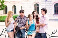 Grupp av lyckliga le tonårs- studenter utanför högskolan Arkivfoton