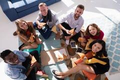 Grupp av lyckliga ledare som har pizza Royaltyfri Foto