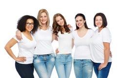 Grupp av lyckliga olika kvinnor i vita t-skjortor royaltyfria bilder