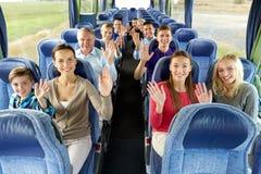 Grupp av lyckliga passagerare som reser med bussen royaltyfria foton