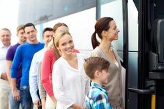Grupp av lyckliga passagerare som stiger ombord loppbussen Royaltyfria Foton