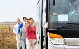 Grupp av lyckliga passagerare som stiger ombord loppbussen arkivbilder