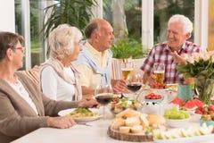 Grupp av lyckliga pensionärer som äter en matställe royaltyfri bild