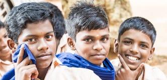 Grupp av lyckliga roliga klasskompisar för barnvänpojkar som ler att skratta på skolan Mång- etniska skolaungar som tycker om kam arkivbild