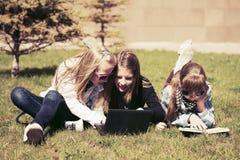 Grupp av lyckliga skolaflickor som ligger på ett gräs i universitetsområde Royaltyfri Bild