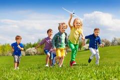 Grupp av lyckliga springungar med det vita flygplanet Royaltyfria Bilder