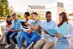 Grupp av lyckliga studenter med anteckningsb?cker och drinkar arkivbilder