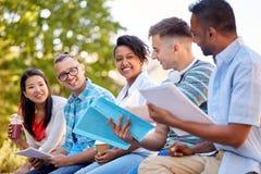 Grupp av lyckliga studenter med anteckningsb?cker och drinkar royaltyfri foto