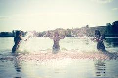 Grupp av lyckliga tonåriga flickor som spelar i vatten Fotografering för Bildbyråer