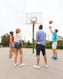 Grupp av lyckliga tonåringar som spelar basket Royaltyfri Fotografi