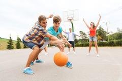 Grupp av lyckliga tonåringar som spelar basket Arkivfoton