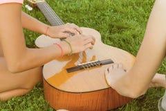 Grupp av lyckliga tonårs- flickor som har rolig det fria med gitarren Sitt på grön gräsmatta i gården, kommet upp med ny musik royaltyfria bilder