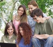 Grupp av lyckliga unga högskolestudenter med bärbara datorn Arkivbild