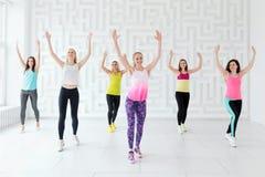 Grupp av lyckliga unga kvinnor med lagledaren som har en cardio genomkörare i konditionstudion royaltyfri foto