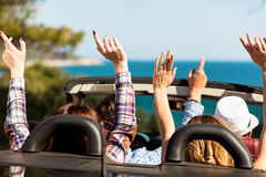 Grupp av lyckliga unga vänner i cabriolet med lyftta händer som kör på solnedgång arkivbilder