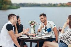 Grupp av lyckliga unga vänner som äter och har gyckel i utomhus- ri royaltyfria bilder