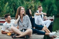 Grupp av lyckliga unga vänner som kopplar av på flodpir royaltyfria bilder