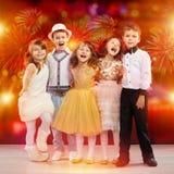 Grupp av lyckliga ungar i feriekläder med fyrverkeribakgrund royaltyfria foton