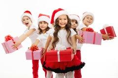 Grupp av lyckliga ungar i julhatt med gåvor Arkivfoto