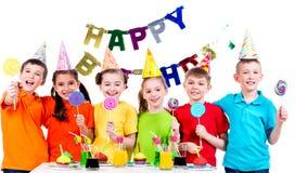 Grupp av lyckliga ungar med färgrika godisar Arkivbild