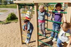 Grupp av lyckliga ungar på barnlekplats fotografering för bildbyråer
