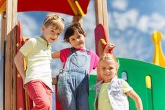 Grupp av lyckliga ungar på barnlekplats arkivbilder