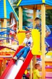 Grupp av lyckliga ungar som glider på färgrik lekplats royaltyfria bilder