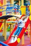 Grupp av lyckliga ungar som glider på färgrik lekplats arkivfoton
