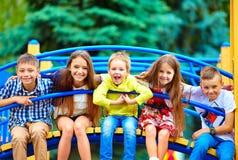 Grupp av lyckliga ungar som har gyckel på lekplats royaltyfria foton