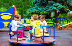 Grupp av lyckliga ungar som har gyckel på karusell på lekplatsen Arkivbild