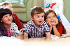 Grupp av lyckliga ungar som hemma håller ögonen på tv:n Royaltyfria Bilder
